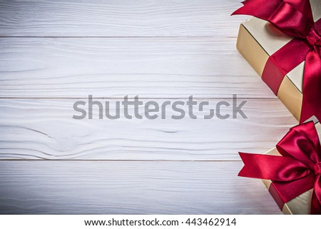 Gift-containers with tied bows on wooden board copy space holidays concept. - stock photo