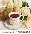Gift, cup of tea, white roses - stock photo