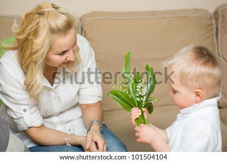 Gift flowers for my mom, baby son and his mother having fun. - stock photo