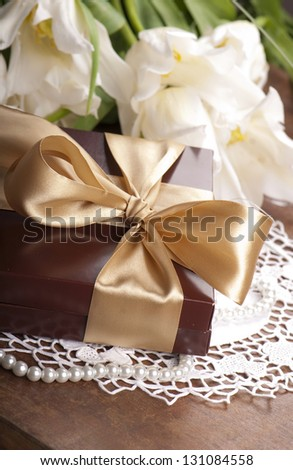 gift in a box with a bow and flowers white tulips on a wooden table