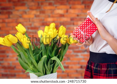 gift in the hands of a girl close-up and a bouquet of tulips International Women's Day. On March 8, Mother's Day, Valentine's Day