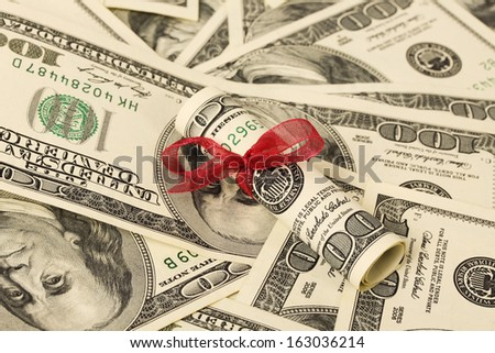 Gift of money with red ribbon on money american hundred dollar bills  - stock photo