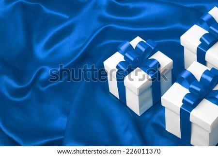 gift on blue satin background. studio shot - stock photo