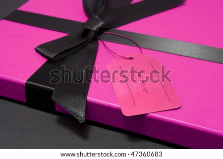Gift or present with pink box and a black ribbon and empty label
