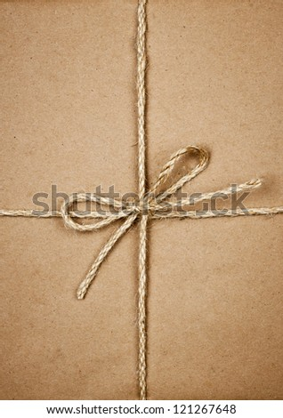 Gift package wrapped in brown paper tied with twine closeup - stock photo