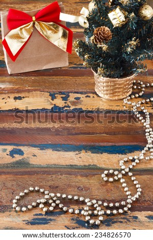 Gift paper package with red golden bow on wooden table near small christmas tree. Selective focus. Copy space - stock photo