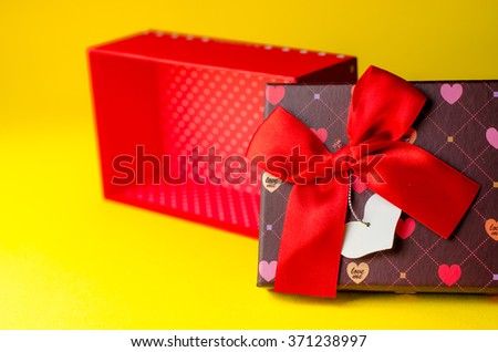 Gift red box for Valentine's Day on a yellow background, hearts
