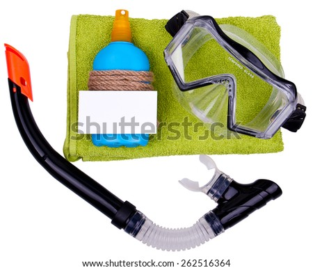 Gift set - green towel, blue bottle of suntan spray and professional dive mask with snorkel. Bottle is decorated with rope. White paper card for your text on the bottle. Isolated. - stock photo