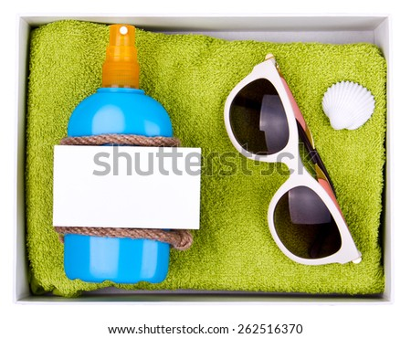 Gift set - green towel, blue bottle of suntan spray and white sunglasses in paper box. Decorated with shell and rope. White paper card for your text on the bottle. Isolated - stock photo