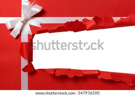 Gift torn open strip, white ribbon bow, red paper background - stock photo
