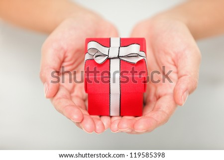 Gift. Woman holding showing gift or christmas gift in her hands. Female hands giving red present. - stock photo