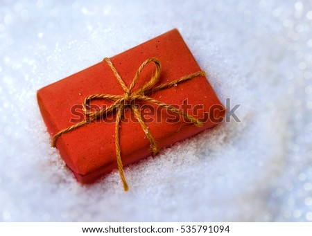 Gift wrapped in paper in the snow. Christmas gift in red paper