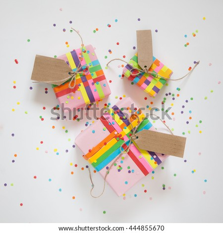 Gift wrapped in paper. Small gifts are packed in colored paper. Colored ribbons. Gift wrapping. White background. View from above. Pastel shades.