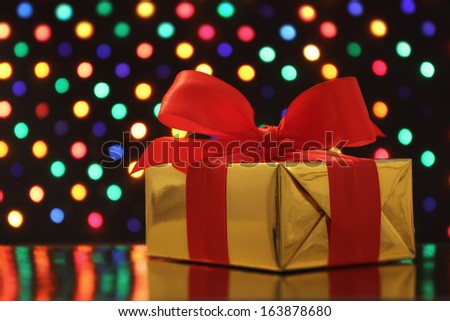 Gift wrapped present with a bow in front of a festive garland lights soft-focus background - stock photo
