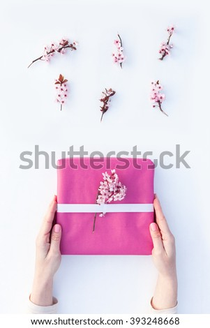 Gift wrapping step by step. Woman packs gifts with pink paper and flowers on white background. Springtime concept. - stock photo