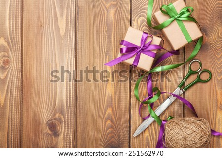 Gift wrapping with boxes and scissors over wooden table with copy space - stock photo