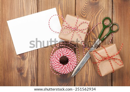 Gift wrapping with greeting card, boxes and scissors over wooden table  - stock photo