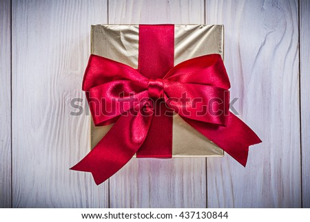 Giftbox in glittery paper with red bow on wood board holidays concept. - stock photo