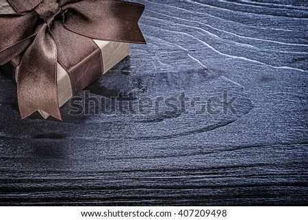 Giftbox with present on wooden board. - stock photo