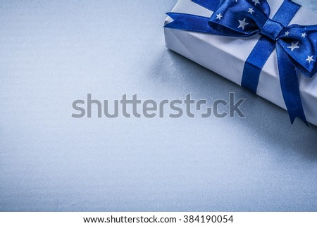 Giftbox with present ribbon on blue background holidays concept. - stock photo
