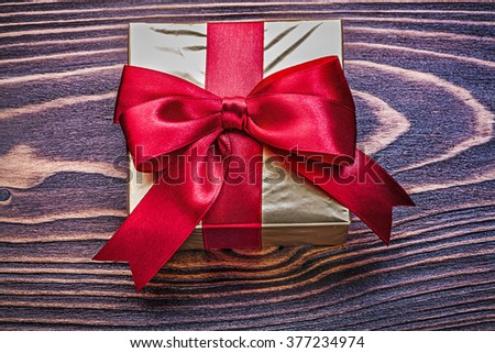 Giftbox wrapped in glittery paper on wooden board. - stock photo