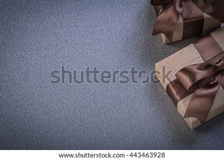 Giftboxes with brown bows on grey background celebrations concept. - stock photo
