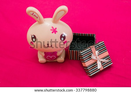 Gifts and stuffed rabbit that was open on a pink background. - stock photo