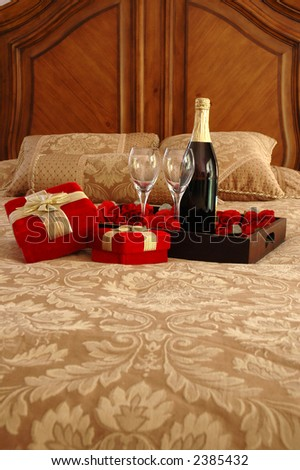 Gifts, champagne, and roses on a bed - stock photo