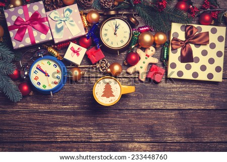 Gifts, cup of coffee and pine branch on a wooden table.  - stock photo