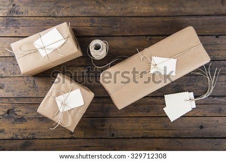 Gifts for Christmas packaged and wrapped on a wooden table - stock photo