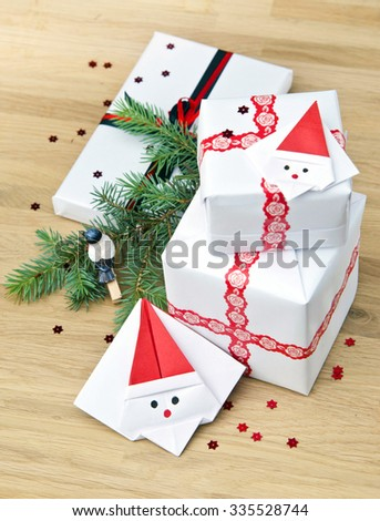 Gifts for Christmas Santa Claus origami envelopes on a wooden table top with tree branches near - stock photo
