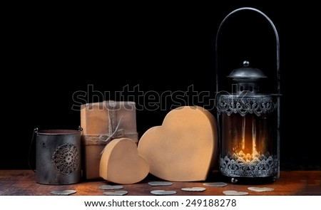 Gifts in paper bags and old burning lamp in vintage style on a wooden background.Metal candle holders cardboard heart.