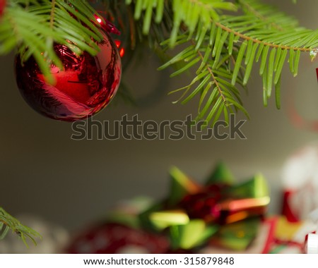 Gifts in the background with a christmas ornament hanging from the tree up front - stock photo