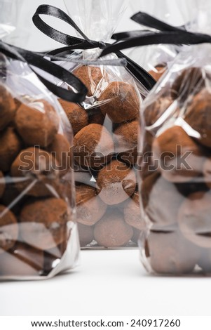 Gifts of Christmas chocolate truffles in luxury plastic bags with black ribbon. Closeup. Shooting on white background in studio. - stock photo
