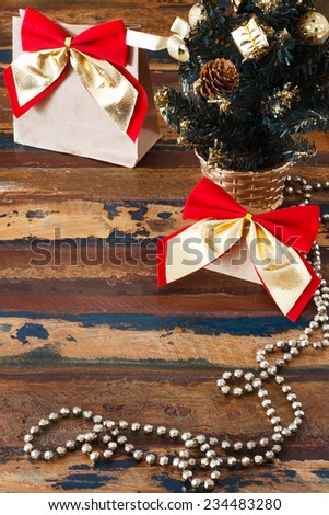 Gifts paper package with red golden bow near small Christmas tree. Selective focus on bow. Copy space - stock photo