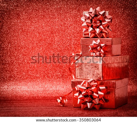 Gifts with ribbon bow on shiny red background. Holidays decoration. Vintage toned picture. Selective focus - stock photo