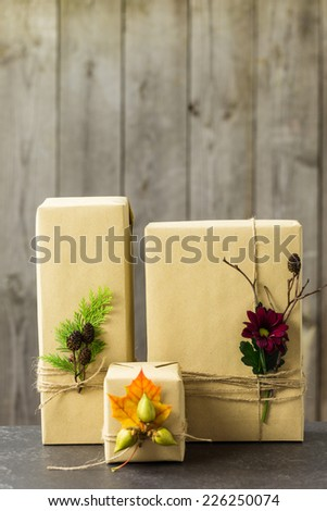 Gifts wrapped in kraft paper, tied with twine and embellished with natural details - stock photo