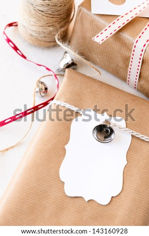 Gifts wrapped in plain paper tied with twine, silver ornaments and a blank gift tag, crafting at home for christmas valentines day - stock photo