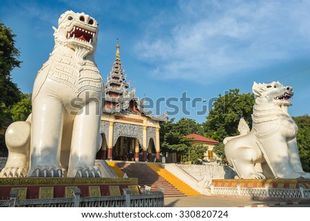 Gigantic Bobyoki Nat guardian statues at central entrance gate to Mandalay Hill Pagoda complex. Amazing architecture of Buddhist Temples in Myanmar (Burma). Travel landscapes and destinations - stock photo