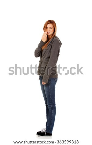 Giggles teenage woman covering her mouth with hand - stock photo