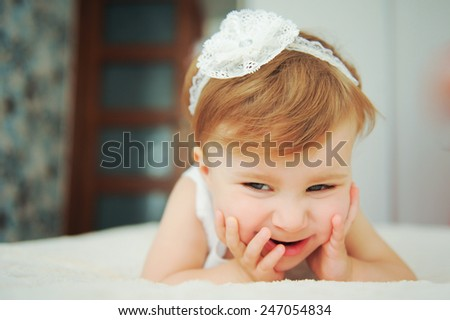 giggling girl laying on bed - stock photo