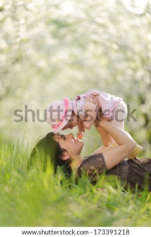 giggling mother and daughter in garden - stock photo