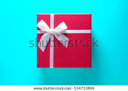 Gigt box with and white ribbon. Valentines day simbols on a blue table background
