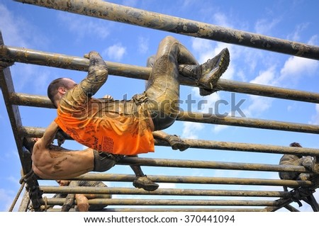 GIJON, SPAIN - JANUARY 31: Farinato Race, extreme obstacle race in January 31, 2016 in Gijon, Spain. People jumping, crawling,passing under a barbed wires obstacles during extreme obstacle race.  - stock photo