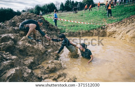 GIJON, SPAIN - JANUARY 31, 2016: Runners into the Farinato Race event, a extreme obstacle race, celebrated in Gijon, Spain, on January 31, 2016. Team helping to cross a mud pit in a test of the race. - stock photo