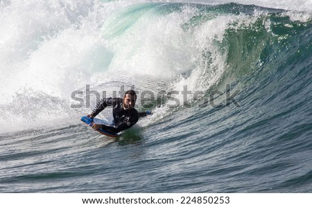 GIJON, SPAIN  Oct, 2014:  Athlete surfing on San Lorenzo beach located in Gijon, in the north of Spain. October 20, 2014