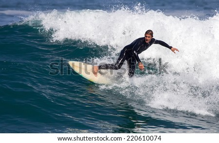 GIJON, SPAIN  Sep, 28:  Unidentified man surfing on a beach located on the outskirts of Gijon. Spain. September 28, 2014 - stock photo