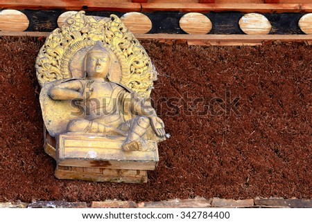 Gilded Buddha relief-wood and red heather wall-shrine on Ponpori Hill-right bank of Trum or Chong Chu river-grounds of the 1073 AD-Khon Konchog Gyalpo built North Seat of Sakya-Grey Soil monast. Tibet - stock photo