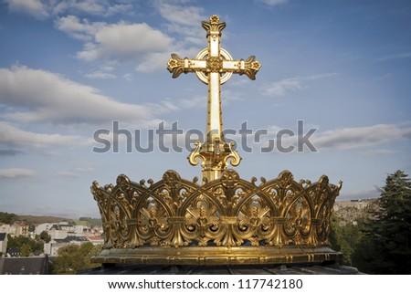 Gilded crown and cross of the dome of the Basilica of Our Lady of the Rosary of Lourdes, France. The crown symbolizes the power and glory of God and is donated by Irish pilgrims many years ago.