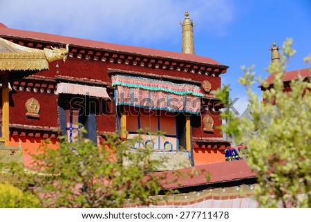 Gilded roofs and decoration -dhvaja or victory banner-makara or crocodile-roundel- atop red roof of building in the courtyard of the AD.642 founded-25000 m2 Jokhang-House of Buddha temple. Lhasa-Tibet - stock photo